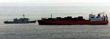 """Flyktningene ble overført fra """"Tampa"""" til marinefartøyet """"HMS Manoora"""" (venstre) 3. september 2001. (Arkivfoto: Scanpix/AP/Dita Alangkara)"""