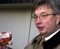 Finansminister Karl Eirik Schjøtt-Pedersen med statsbudsjettet på en CD. (Fot: Scanpix)