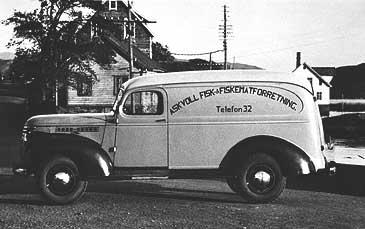 Askvoll Fisk & Fiskematforretning vart grunnlagt 1945 av Lars, Arnfinn og Leif Bauge. Dei dreiv fiskemottak og produksjon av fiskemat, som dei m.a. selde frå denne fiskebilen. (Foto: © Fylkesarkivet)