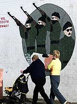 Innbyggere går forbi et IRA-veggbilde. (Foto: Scanpix/AP/Paul Faith)