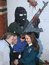 Flere skolejenter leker foran et IRA-veggbildet i Belfast 23. oktober 2001. (Foto: Scanpix/AP/Paul Faith)