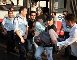 En såret tenåringspike bæres ut av bussen. (Foto: Scanpix/AP)