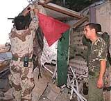 Palestinske politimenn henger et palestinsk flagg opp ved de ødelagte kontorene til palestinske sikkerhetsstyrker i Qalqilya, mandag 5. november. (Foto: AP/Nasser Ishtayeh)