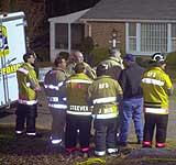 Redningsmannskaper og brannmenn kikker på huset til den 94 år gamle kvinnen som er smittet av miltbrann. (Foto: AP)