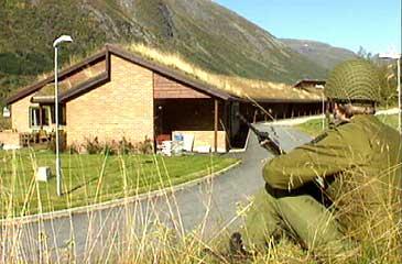 Soldat på øving vaktar aministrasjonsbygget til HV-10 på Skei. (Foto: NRK)
