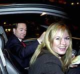 En smilende Kjell Inge Røkke og Celina Midelfart forlater Kværners generalforsamling. (Foto: Scanpix/Thomas Bjørnflaten)
