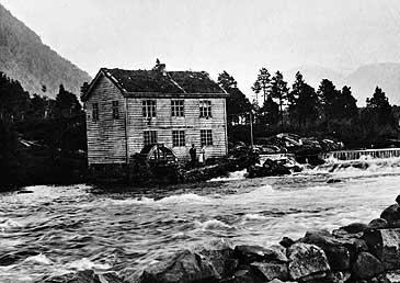 Heggen Møbelfabrikk i 1909. Fabrikkhuset måtte flyttast då elva vart demd opp for å gje kraft til Eid Elektrisitetsverk. (©Fylkesarkivet)
