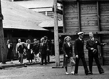 Prinsesse Astrid (i følgjet t.v.) og Kong Haakon VII (i miden t.h.) får omvising på NACO i Høyanger i 1949. (© Fylkesarkivet)