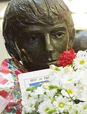 George Harrison, som en del av en Beatles-statue i Liverpool er tildekket med blomster. George Harrison døde av kreft 29. november. (Foto: AP Photo/Alastair Grant).