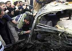 Palestinere samlet rundt den utbombede bilen. (Foto: AP/SCANPIX)