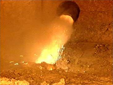 Tilføring av oksid i ein elektrolyseomn. (Foto: NRK)