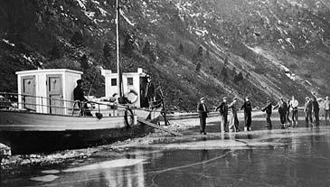 Rutebåten på Årdalsvatnet står fast, og mennene må ut på glattisen. Biletet er frå 1938. (Foto © Fylkesarkivet)