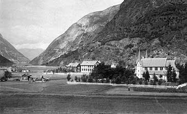 Lærdalsøyri i 1910. Det kvite bygget i midten er skulen, og til venstre for den ligg posthuset. Til høgre er Hauge kyrkje. (Foto © Fylkesarkivet)