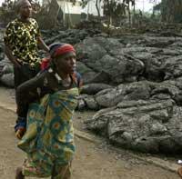 Et ektepar går over varm lava på vei tilbake til sitt hjem i Goma(foto: Sayyid Azim/ap/scanpix)