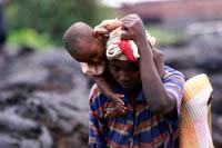 En mor løfter sitt barn høyt over den varme lavaen ved Goma. (Foto: Karel Prinsloo, AP)