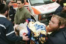 En uidentifisert kvinne bæres inn i ambulansen. (Foto: Scanpix/AP/Lefteris Piterakis)