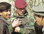 Et britisk medlem av de internasjonale fredsbevarende styrkene i Kabul snakker med afghanske sivile. (Foto: Scanpix/AP/Michail Metzel)