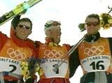 Frode Estil og Thomas Alsgaard flankerer juksemaker Mühlegg etter jaktstarten i OL.