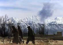 Anghanere spaserer i utkanten av Paktia med mørke skyer fra flyangrep i horosonten. Foto: Lefteris Pitarakis, AP/Scanpix)