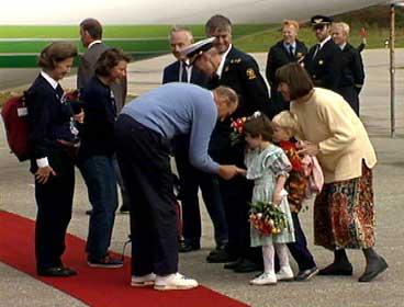Kongeleg følgje på Anda i 1993. Framme f.v.: Dronning Sonja, Prinsesse Märtha Louise og Kong Harald som får blomar. I bakgrunnen står m.a. ordførar Nils R. Sandal. (Foto: Aasulv C. Austad, NRK)