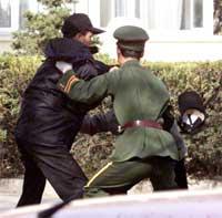 En kinesisk soldat prøver å stoppe en av nordkoreanerne i det han og 24 andre stormet den spanske ambassaden. (Foto: AP)