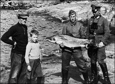 Løytnant Kaufmann (t.h) og oppassar Meyer var stasjonert på Eide. Dei ville gjerne bli fotografert med ein laks i hendene. Denne ruggen er det Johannes Eide som har teke i nota si. I bakgrunnen er kloggfabrikken og kvernhuset. (Foto © Fylkesarkivet)
