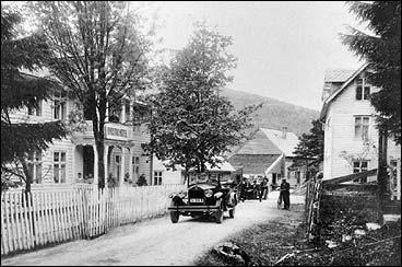 Bygstad hotell på Kviteneset i 1927. Lengst bak er tønnefabrikken. I huset til høgre var det butikk i første etasje. Bilen tilhøyrer Halvard Leirvik. (Foto © Fylkesarkivet)