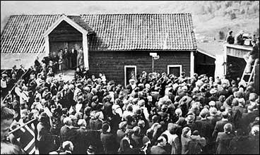 Bygdefolk samla kring radioapparat på Reita for å høyre kronprins Olav sin tale frå London frigjeringsdagen 8. mai 1945. (Foto © Fylkesarkivet)