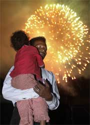 En mann og hans datter feirer uavhengigheten for Øst-Timor mens fyrverkeri smeller i bakgrunnen. (Foto: AP/Scanpix)
