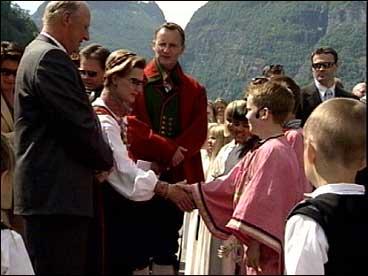 I Aurland fekk kongen og dronninga sjå jubileumsspelet på torget der 10 år gamle Brede Tokvam hadde rolla som kong Sverre. Etterpå fekk Brede helse på den ekte kongen og dronninga. I bunad i midten på biletet står ordførar Ivar Bjarne Underdal. (Foto: NRK)