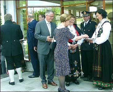 Kongen (i bakgrunnen) gav toppkarakter til gamalosten. I forgrunnen: Dronning Sonja smakar portvinsmarinert gamalost! Fylkesmann Oddvar Flæte og politimeister Kjell Ese følgjer spent med.
