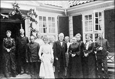 Hovudinngangen på futegarden Askelund kring år 1900. I døropninga står Hans Bonnevie Angell og kona Petra Nathalie. Til høgre for dei står bonde Ola Johannesson Sjøtun (1830-1915). (Foto © Fylkesarkivet)