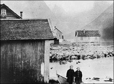 Huset til høgre vart brukt til forsamlingslokale i Balestrand før Ungdomshuset vart bygt. Biletet er frå tidleg på 1900-talet, og gutane i framgrunnen er sønene til distriktslege Køste. (Foto © Fylkesarkivet)