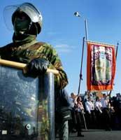Fra Orange-ordenens parade gjennom Belfast i dag. Demonstranter passerer britisk soldat (Reuters)