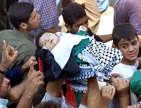Palestinere bærer liket av en to måneder gammel baby som ble drept i angrepet natt til 23. juli i Gaza. (Foto: Suhaib Salem, Reuters)