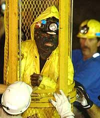 Den tredje av de ni gruvearbeiderne reddes ut ved hjelp av redningskapselen i morges. (Foto: Reuters/Guy Wathen)