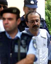 Greske Pavlos Serifis (høyre) forlater rettslokalet i Athen 25. juli 2002. Serifis var ifølge politiet involvert i drapet på CIA-stasjonssjefen Richard Welch i 1975. (Foto: Reuters/Yiorgos Karahalis)