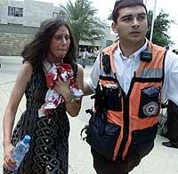 En skadd kvinne hjelpes ut av kafeterian ved universitetet i Jerusalem onsdag 31. juli 2002. (Foto: Reuters/Nir Elias)