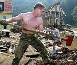 En tysk soldat spar bort gjørme i ruinene av et hus i landsbyen Wesenstein. Foto: Fabrizio Bensch, Reuters