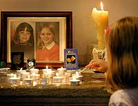 En ung jente tenner et lys for de to skolejentene Jessica Chapman og Holly Wells i kirken i Soham søndag 18. august 2002. (Foto: Reuters/Dan Chung)