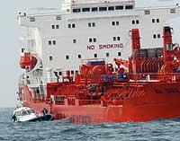 """Franske etterforskere og en advokat fra de norske eierne klatrer om bord i """"Bow Eagle"""" onsdag 28. august 2002. (Foto: Reuters)"""