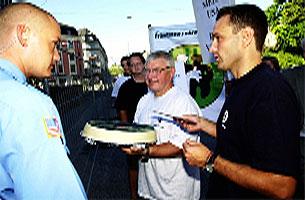 Daglig leder i Fremtiden i våre hender, Arild Hermstad (th) og Erling Onsøyen på vei inn for å overlevere en kake til en av sikkerhetsvaktene ved den amerikanske ambassaden i Oslo. (Foto: Cornelius Poppe, Scanpix)