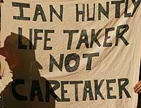 Demonstranter holdt opp flagg for å protestere utenfor rettslokalet tirsdag 10. september 2002. (Foto: Reuters/Darren Staples)