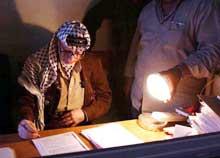 Palestinernes president Yasir Arafat signerer papirer i lyset fra en lommelykt. (Foto: Scanpix/Reuters/Hussein Hussein