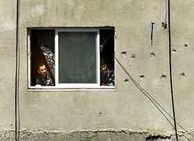 En palestiner ser ut av et vindu i president Arafats hovedkvarter idet israelerne trekker seg vekk. Foto: Reinhard Krause , Reuters