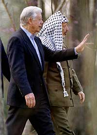 Fredsprisvinner Jimmy Carter viser frem hagen sin til palestinernes president Yasir Arafat 5. mars 1997. (Arkivfoto: Reuters/John Kuntz)