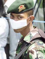 En soldat med munnbind utenfor et likhuset ved et av Balis sykehus. (Foto: Reuters/Darren Whiteside)