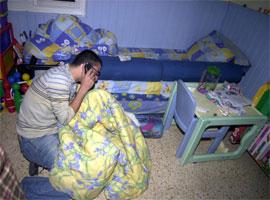 En fortvilet far på barnerommet der hans to barn ble skutt og drept. (Reuters-Scanpix)