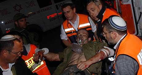 En skadd israeler frakter til en ambulanse etter skytingen i Hebron i kveld. (Foto: Reuters/FLASH 90/Yossi Zamir)