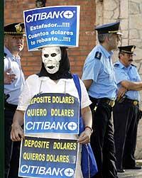 """En maskert demonstrant holder opp en plakat hvor det står skrevet """"Jeg satte inn dollar, jeg vil ha ut dollar"""" foran presidentpalasset i Buenos Aires 18. november 2002. (Foto: Reuters/Enrique Marcarian)"""